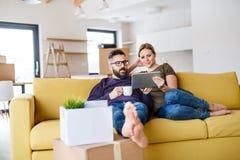 Μια νεολαία συνδέει με τη συνεδρίαση ταμπλετών και καφέ στον καναπέ, που κινείται στο νέο σπίτι στοκ φωτογραφία με δικαίωμα ελεύθερης χρήσης