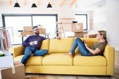 Μια νεολαία συνδέει με τη συνεδρίαση ταμπλετών και καφέ στον καναπέ, που κινείται στο νέο σπίτι στοκ φωτογραφίες με δικαίωμα ελεύθερης χρήσης