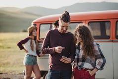 Μια νεολαία συνδέει σε ένα roadtrip μέσω της επαρχίας, χρησιμοποιώντας το χάρτη στο smartphone στοκ φωτογραφία με δικαίωμα ελεύθερης χρήσης