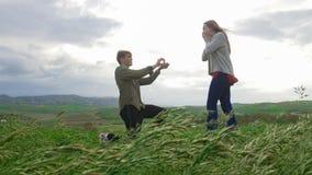Μια νεολαία συνδέει στον τομέα - ένα άτομο που κάνει μια πρόταση με τη φίλη του στοκ εικόνες με δικαίωμα ελεύθερης χρήσης