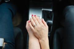 Μια νεολαία συνδέει τα ερωτευμένα χέρια εκμετάλλευσης, εκμετάλλευση στο μοχλό μετατόπισης που πηγαίνει στο οδικό ταξίδι Ένα άτομο Στοκ Εικόνα