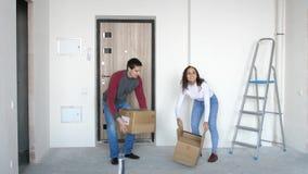 Μια νεολαία συνδέει την κίνηση σε ένα νέο σπίτι Ένα χαρούμενο ζεύγος αγκαλιάζει και στέκεται στο κατώφλι 3840x2160, 4K απόθεμα βίντεο