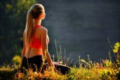 Μια νεολαία ξανθή σε μια κόκκινη κορυφή κάθεται στη χλόη για την ικανότητα στη φύση Μια φίλαθλος προετοιμάζεται για τη γυμναστική Στοκ Φωτογραφία