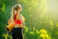 Μια νεολαία ξανθή σε μια κόκκινη κορυφή και μαύρα εσώρουχα κρατά ένα χαλί για μια πηγή στη φύση Μια γυναίκα προετοιμάζεται για τη Στοκ εικόνες με δικαίωμα ελεύθερης χρήσης