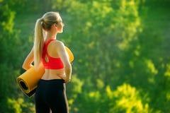 Μια νεολαία ξανθή σε μια κόκκινη κορυφή και μαύρα εσώρουχα κρατά ένα χαλί για μια πηγή στη φύση Μια γυναίκα προετοιμάζεται για τη Στοκ Εικόνες