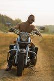 Μια νεολαία συνδέει ερωτευμένο σε μια μοτοσικλέτα στον τομέα στοκ φωτογραφίες με δικαίωμα ελεύθερης χρήσης