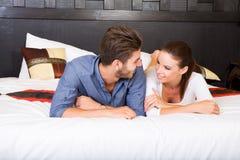 Μια νεολαία συνδέει να βρεθεί στο κρεβάτι σε ένα ασιατικό δωμάτιο ξενοδοχείου ύφους Στοκ Φωτογραφίες