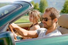 Μια νεολαία συνδέει σε ένα μετατρέψιμο αυτοκίνητο στοκ εικόνες