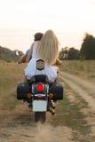 Μια νεολαία συνδέει στον τομέα δίπλα στη μοτοσικλέτα Στοκ Εικόνες