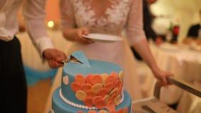 Μια νύφη και ένας νεόνυμφος κόβουν το γαμήλιο κέικ τους φιλμ μικρού μήκους