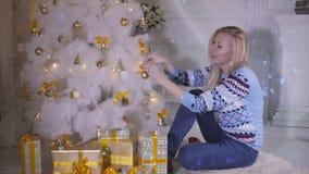Μια ξανθή γυναίκα κάθεται κάτω από ένα χριστουγεννιάτικο δέντρο και παρουσιάζει φιλμ μικρού μήκους