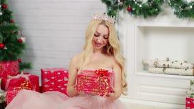 Μια ξανθή γυναίκα που εξετάζει ένα όμορφο χριστουγεννιάτικο δώρο φιλμ μικρού μήκους