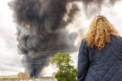 Μια ξανθή γυναίκα που προσέχει μια μεγάλη πυρκαγιά Στοκ εικόνες με δικαίωμα ελεύθερης χρήσης