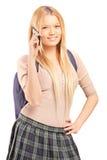 Μια ξανθή γυναίκα σπουδαστής με μια σχολική τσάντα που μιλά σε ένα τηλέφωνο Στοκ Εικόνες