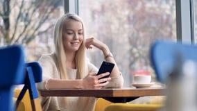 Μια ξανθή γυναίκα χαμογελά στην οθόνη smartphone της απόθεμα βίντεο