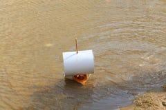 Μια ξύλινη βάρκα παιχνιδιών με ένα πανί του εγγράφου επιπλέει κατά μήκος των κυμάτων στην ακτή, μια ηλιόλουστη ημέρα Στοκ φωτογραφίες με δικαίωμα ελεύθερης χρήσης