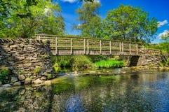 Μια ξύλινη γέφυρα για πεζούς που διασχίζει έναν ποταμό στην αγγλική περιοχή λιμνών στοκ φωτογραφία με δικαίωμα ελεύθερης χρήσης