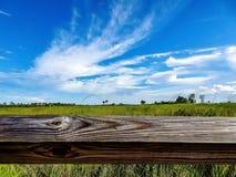 Μια ξύλινη θέση φρακτών σε έναν τομέα χλόης ενάντια σε έναν μπλε ουρανό Στοκ φωτογραφίες με δικαίωμα ελεύθερης χρήσης