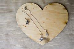 Μια ξύλινη καρδιά για την ημέρα βαλεντίνων ` s με τα ασημένια σκουλαρίκια με τα διαμάντια, πολύτιμοι λίθοι, rhinestones στοκ φωτογραφίες με δικαίωμα ελεύθερης χρήσης