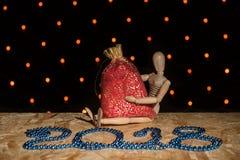 Μια ξύλινη μαριονέτα κουκλών κάθεται και κρατά μια κόκκινη νέα τσάντα έτους ` s με το α Στοκ Φωτογραφία