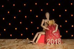 Μια ξύλινη μαριονέτα κουκλών κάθεται και κρατά μια κόκκινη τσάντα με ένα δώρο και ένα θόριο Στοκ Φωτογραφίες
