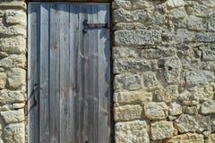 Μια ξύλινη πόρτα με τις αρθρώσεις μετάλλων εγκαθίσταται στον τοίχο μιας αρχαίας πέτρας Στοκ Εικόνες