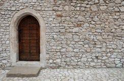 Μια ξύλινη πόρτα με τη δειγμένη γοτθική αψίδα ύφους σε έναν τοίχο πετρών Στοκ Εικόνες