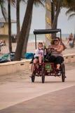 Μια οικογένεια οδηγά ένα τρίκυκλο στο θαλάσσιο περίπατο από την παραλία στοκ εικόνες