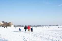 Μια οικογένεια στο σχολείο τρέχει σε έναν χιονώδη τομέα κάτω από έναν μπλε σαφή ουρανό στοκ εικόνες