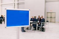Μια ομάδα ανθρώπων συζητά ένα πρόγραμμα Τα άτομα διαπραγματεύονται στον πίνακα Κενό μπλε πιάτο Προσωπικό και συνάδελφοι συνεδρίασ στοκ φωτογραφία με δικαίωμα ελεύθερης χρήσης