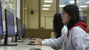 Μια ομάδα ασιατικών σπουδαστών χρησιμοποιεί τους υπολογιστές κατά τη διάρκεια της κατάρτισης απόθεμα βίντεο