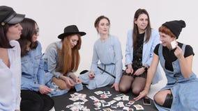 Μια ομάδα γυναικών κάθεται στο πάτωμα Οι γυναίκες επιλέγουν το ύφος του ιματισμού στις εικόνες απόθεμα βίντεο