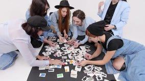 Μια ομάδα γυναικών κάθεται στο πάτωμα Οι γυναίκες επιλέγουν το ύφος του ιματισμού στις εικόνες φιλμ μικρού μήκους