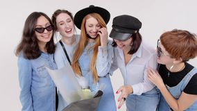 Μια ομάδα γυναικών στο τζιν ντύνει την τοποθέτηση σε ένα άσπρο στούντιο Μια δέσμη των λουλουδιών στα χέρια τους Γυναίκες στα γυαλ απόθεμα βίντεο