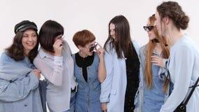 Μια ομάδα γυναικών στο τζιν ντύνει την τοποθέτηση σε ένα άσπρο στούντιο Γυναίκες στα γυαλιά και τα καπέλα φιλμ μικρού μήκους