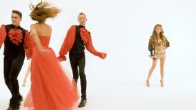 Μια ομάδα επαγγελματικών δραστών που χορεύουν σε ένα άσπρο υπόβαθρο Ο τραγουδιστής κοριτσιών στο κόκκινο φόρεμα Δύο νεαροί άνδρες απόθεμα βίντεο