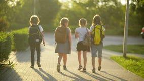 Μια ομάδα επιστροφής σπουδαστών στο σχολείο από κοινού Έχουν πολλή διασκέδαση μιλώντας ο ένας στον άλλο απόθεμα βίντεο