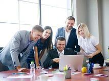 Μια ομάδα εργαζομένων γραφείων που εξετάζουν τις ιδέες σχετικά με ένα lap-top Στοκ Εικόνες