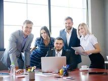 Μια ομάδα εργαζομένων γραφείων που εξετάζουν τις ιδέες σχετικά με ένα lap-top Στοκ φωτογραφία με δικαίωμα ελεύθερης χρήσης