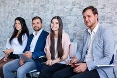 Μια ομάδα ευτυχών ανθρώπων, συνεδρίαση και χαμόγελο, κρατώντας τα κινητά τηλέφωνα και μια ταμπλέτα indoors Στοκ Φωτογραφίες