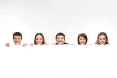 Μια ομάδα εφήβων που κρύβουν πίσω από ένα άσπρο έμβλημα Στοκ φωτογραφία με δικαίωμα ελεύθερης χρήσης