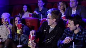 Μια ομάδα εύθυμων νέων φίλων ρίχνει popcorn στον κινηματογράφο φιλμ μικρού μήκους