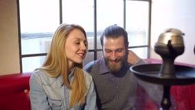 Μια ομάδα εύθυμων φίλων που στηρίζονται σε έναν καφέ, καπνίζουν hookah, μιλούν και γελούν φιλμ μικρού μήκους