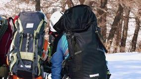 Μια ομάδα καλά εκπαιδευμένων ορειβατών στέκεται μαζί σε μια μικρή χιονισμένη άκρη, για παράδειγμα και ελέγχει εάν απομακρύνθηκαν  φιλμ μικρού μήκους