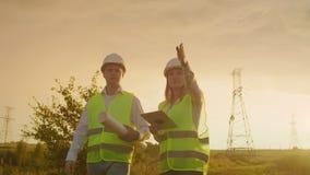 Μια ομάδα μηχανικών σε υψηλής τάσεως εγκαταστάσεις παραγωγής ενέργειας με μια ταμπλέτα και τα σχέδια περπατούν και συζητούν ένα σ απόθεμα βίντεο