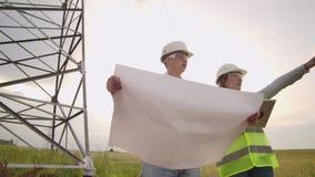Μια ομάδα μηχανικών σε υψηλής τάσεως εγκαταστάσεις παραγωγής ενέργειας με μια ταμπλέτα και τα σχέδια περπατούν και συζητούν ένα σ φιλμ μικρού μήκους