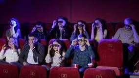 Μια ομάδα νέων βάζει τα γυαλιά για να προσέξει έναν τρισδιάστατο κινηματογράφο σε μια κινηματογραφική αίθουσα απόθεμα βίντεο