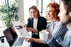 Μια ομάδα νέων επιχειρηματιών με τη συνεδρίαση lap-top σε ένα γραφείο, ομιλία στοκ φωτογραφίες με δικαίωμα ελεύθερης χρήσης