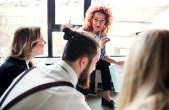 Μια ομάδα νέων επιχειρηματιών που κάθονται στο πάτωμα σε ένα γραφείο, ομιλία στοκ φωτογραφία