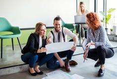 Μια ομάδα νέων επιχειρηματιών που κάθονται στο πάτωμα σε ένα γραφείο, ομιλία στοκ εικόνες
